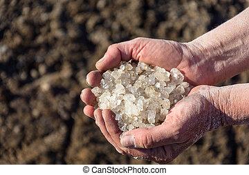 Baskunchak Lake Salt. - A handful of coarse salt on a gray...
