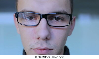 Serious guy with glasses look at camera clous-up HD
