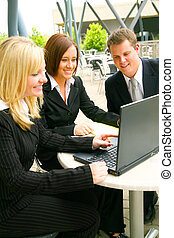 Business Team Looking At Laptop - blond business woman...
