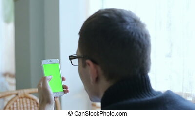 The guy in glasses holding a phone with green b