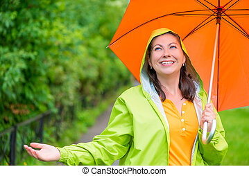 portrait of a beautiful girl with an umbrella and a raincoat...
