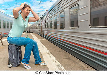 frustrated woman looking at the passing train on which she...
