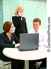 Business Woman With Two Associates On Computer - blond...
