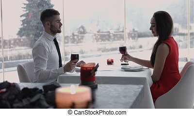 Caucasian couple smiling and toasting wine glasses in a...