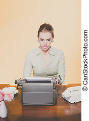 Vintage 1950 blonde secretary woman sitting behind desk working on typewriter. High angle view.