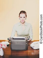 Vintage 1950 blonde secretary woman sitting behind desk working on typewriter. Looking towards camera. High angle view.