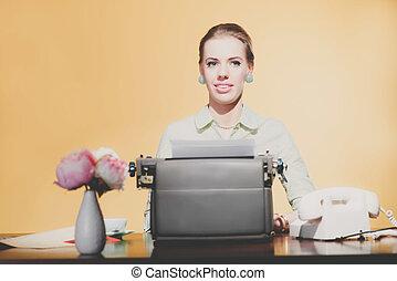 Smiling retro 1950 blonde secretary woman sitting behind desk working on typewriter.