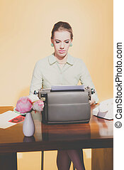Retro 50s young blonde secretary woman sitting behind desk working on typewriter.