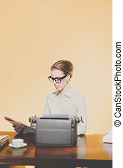 Vintage 1950 young secretary sitting behind desk reading newspaper.
