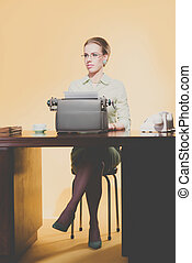 Vintage 1950 young secretary woman behind desk typing on typewriter.