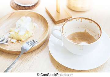 empty cup of coffee and soiled cake plate on table