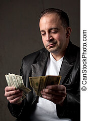 Shady Cash Earnings - A shady looking man counting a handful...