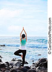 Biracial teen standing on rock by ocean doing yoga -...