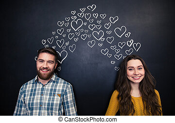 Happy couple standing over background of chalkboard with...