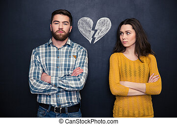 Couple after argument standing separately over blackboard...