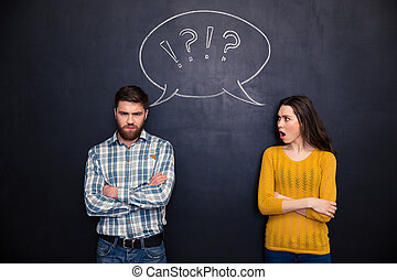 Frowning couple standing after argument over chalkboard...