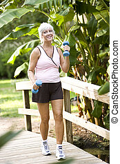 Woman exercising in park walking with hand weights - Woman...