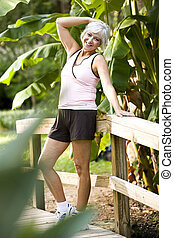 Woman in workout clothes standing on bridge in park