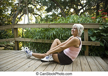 Mature woman stretching and exercising in park