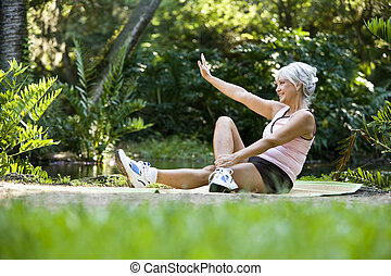 Woman on mat doing stretching exercises outdoors - Woman in...
