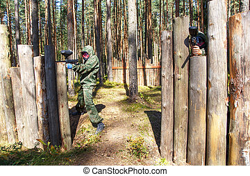 Two shooters with paintball guns defend wooden fortress