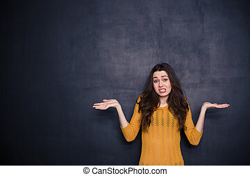 Young woman shrugging shoulders over black background