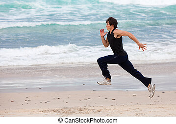 Young Man Running on Beach - Full length profile view of a...