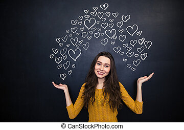 Beautiful woman holding drawing hearts on palms over...