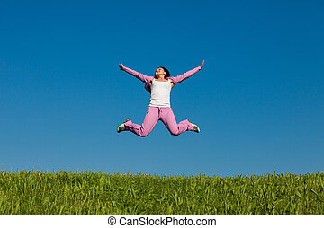 Leaps of joy - RealWoman jumping against blue sky