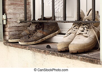 Muddy fashion trainers drying on a window sill. Vintage retro look.