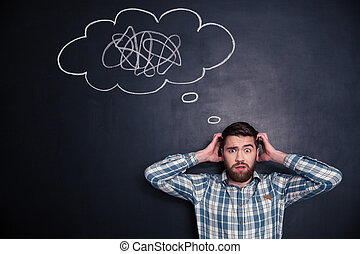 Confused man thinking about problem with black board behind...
