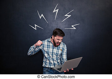 Aggressive man going to break laptop over chalkboard...