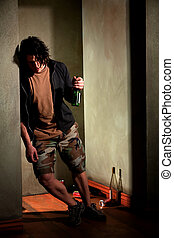 Drunk young man leaning on a wall with beer bottle