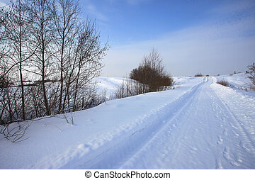 Winter snowy rural road and blue sky landscape