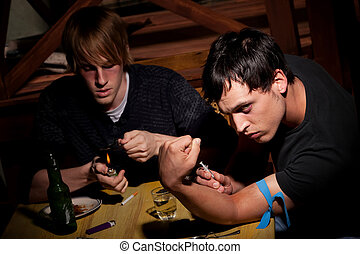 Two men preparing heroin - Two men with heroin cooking in a...