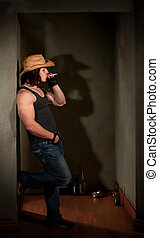 Smoking man in cowboy hat leaning on wall