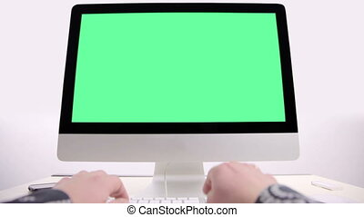 Man hand on keyboard with green screen monitor in the office