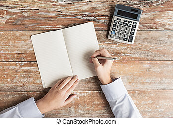 close up of hands with calculator and notebook - business,...