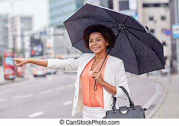 happy african woman with umbrella catching taxi - business...