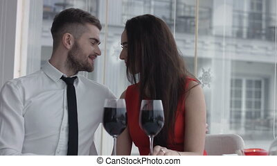 Couple with wine glass sitting in restaurant