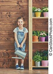girl caring for her plants - Cute child girl caring for her...