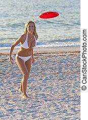 Beautiful Blond Woman In Bikini Playing Frisbee At The Beach