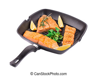 Fried salmon fillet in pan with lemon Isolated on a white...
