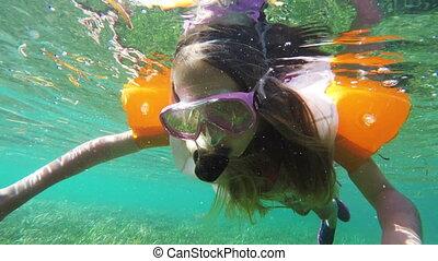 Young girl scuba diver - Girl scuba diver touches coral...