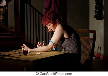 Injecting heroin - Woman wih tracks on her arm injecting...