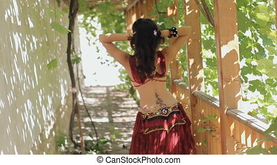 Attractive woman with tattoos dancing belly dance in gazebo...