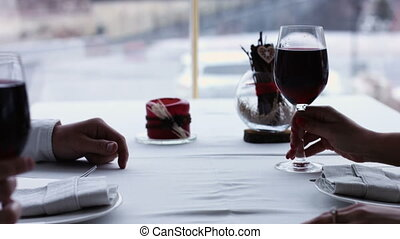 Young Couple Toasting Wine Glass In Restaurant. Dating. Young man and woman on romantic dinner drinking at restaurant, celebrating valentine day.