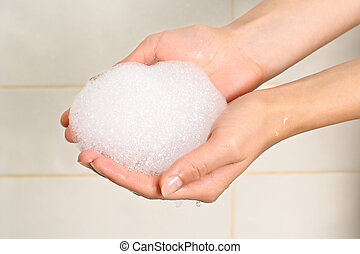 Soap suds in palms - Woman hands holding soap suds on...