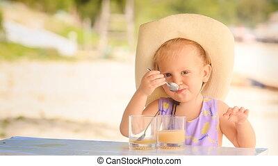 Little Girl in Large Hat Drinks Juice Looks Backwards