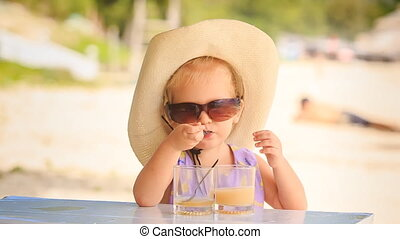 Little Girl in Hat Drinks Juice Takes off Sunglasses